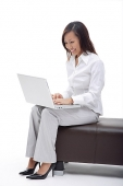 Business woman sitting on bench, using laptop - Asia Images Group