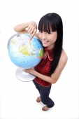 Young woman holding and pointing at globe, smiling at camera - Asia Images Group