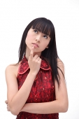 Young woman, finger on chin, looking up - Asia Images Group