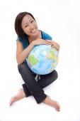 Woman holding globe, sitting cross-legged - Asia Images Group