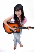 Young woman with guitar, smiling at camera - Asia Images Group