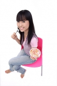 Young woman sitting, holding bowl of ice cream - Asia Images Group