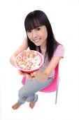 Young woman offering bowl of ice cream - Asia Images Group