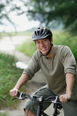 Man on a bicycle, smiling at camera - Asia Images Group