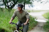 Man cycling on nature path, smiling - Asia Images Group