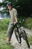 Man standing next to bicycle - Asia Images Group