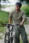 Man with bicycle, outdoors - Asia Images Group