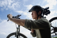 Man carrying bicycle - Asia Images Group