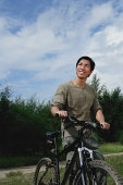 Man with bicycle, outdoors, smiling - Asia Images Group