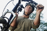 Man carrying bicycle, low angle view - Asia Images Group