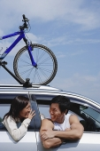 Couple sitting in car, bicycle on the roof - Asia Images Group