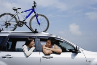Couple sitting in car, leaning out of the windows, bicycle on the roof - Asia Images Group