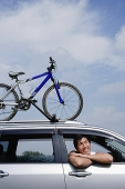 Man sitting in car, leaning out of window, bicycle on the roof of car - Asia Images Group