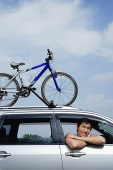 Man leaning out of car window, bicycle on the roof of car - Asia Images Group