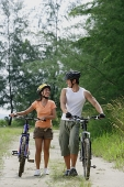 Couple walking with bicycles, looking at each other - Asia Images Group