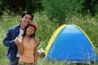 Couple smiling at camera, tent in the background - Asia Images Group
