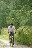 Man cycling on nature path - Asia Images Group