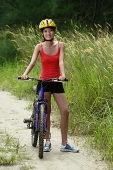 Woman standing with bicycle, smiling at camera - Asia Images Group