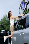 Woman standing on car, securing bike on top of car - Asia Images Group