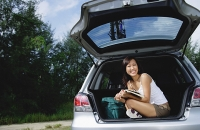 Woman sitting in boot of car, holding magazine - Asia Images Group