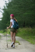 Woman on hiking trail, looking over shoulder at camera - Asia Images Group
