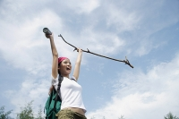 Female hiker, holding hiking stick in air, smiling - Asia Images Group