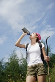 Female hiker drinking from bottle, low angle view - Asia Images Group