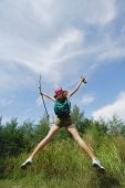 Female hiker, jumping, arms outstretched - Asia Images Group
