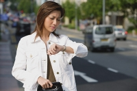 Woman standing by road, looking at watch - Asia Images Group