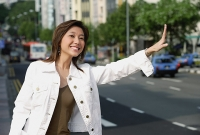 Woman standing by road, waving for taxi - Asia Images Group