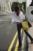 Woman standing by road, waving for taxi, rear view - Asia Images Group