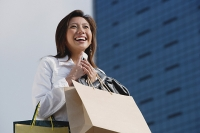 Woman carrying shopping bags, holding mobile phone, smiling - Asia Images Group