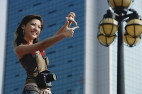 Woman with camera, framing a shot with her fingers - Asia Images Group