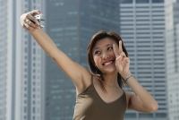 Woman holding digital camera, taking a picture of herself - Asia Images Group