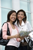 Two women with map, smiling at camera - Asia Images Group