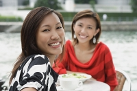 Women at sidewalk cafe, smiling at camera - Asia Images Group