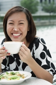 Young woman with cappuccino cup, foam on her nose - Asia Images Group