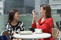 Two women at outdoor cafe, using a camera - Asia Images Group