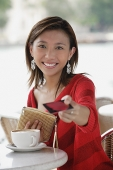 Young woman at cafe, holding credit card towards camera - Asia Images Group