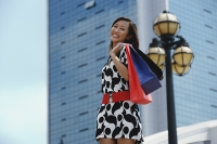 Woman carrying shopping bags, smiling at camera - Asia Images Group
