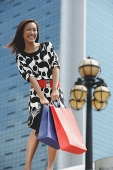 Woman carrying shopping bags, smiling - Asia Images Group