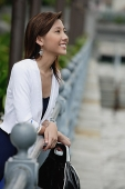 Woman leaning on railing, looking away - Asia Images Group