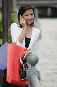 Woman leaning on railing, carrying shopping bags, using mobile phone - Asia Images Group