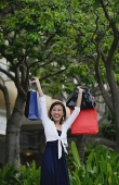 Woman with shopping bags, arms outstretched - Asia Images Group