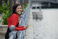 Woman leaning on railing, listening to MP3 player, smiling at camera - Asia Images Group