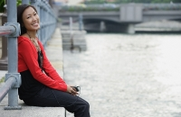 Woman sitting by river, listening to MP3 player, smiling at camera - Asia Images Group