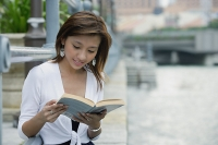 Woman sitting by river, reading a book - Asia Images Group