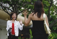 Two women walking, waving at each other - Asia Images Group