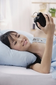 Young woman lying on bed, looking at alarm clock, smiling - Asia Images Group