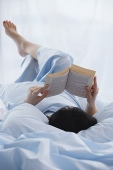 Young woman lying in bed, reading a book - Asia Images Group